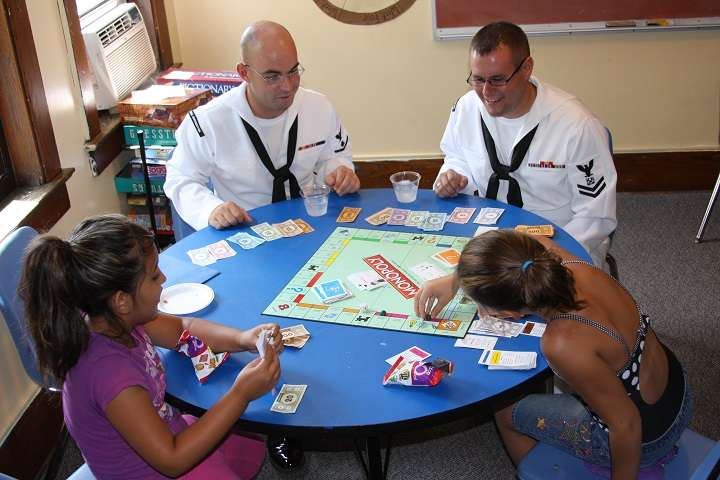 110713-N-NT881-124 ROCHESTER, N.Y. (July 13, 2011) Personnel Specialist 2nd Class James Vail, left, and BoatswainÕs Mate 2nd Class Nathaniel Eaton, both assigned to Navy Operational Support Center Rochester, play board games with children at the Cameron Community Ministries during Rochester Navy Week, one of 21 Navy Weeks planned across America this year. Navy Weeks are designed to showcase the investment Americans have made in their Navy and increase awareness in cities that do not have a significant Navy presence. (U.S. Navy photo by Chief Mass Communication Specialist Steve Carlson/Released)